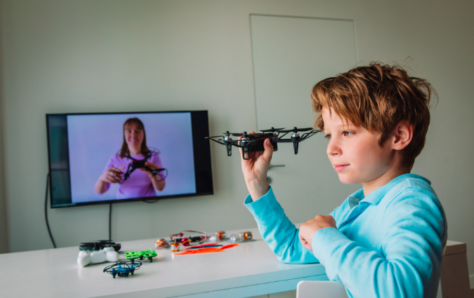 young boy playing with a drone