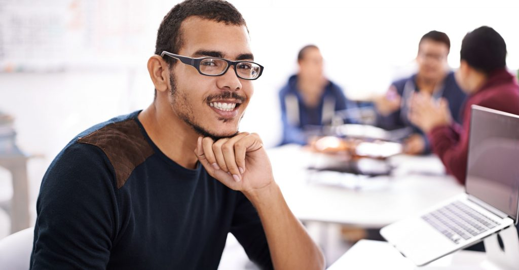 coding learner smiling in front of a computer